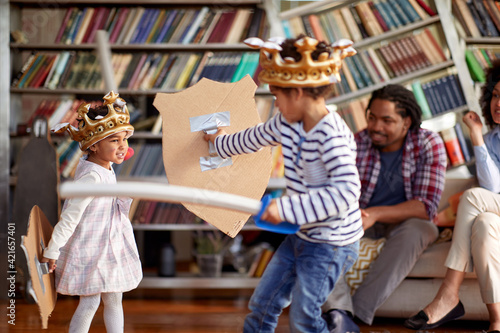 Obraz Children dressed like knights are fighting with swords while being watched with their parents at home. Family, home, playtime - fototapety do salonu