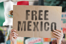 """The Phrase """" Free Mexico """" On A Banner In Men's Hand With Blurred Mexican Flag On The Background. Protest. Riot. Violence. Economic Crisis. Collapse. Politics. Streets. Save. Cruelty"""