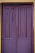 Vertical Shot Of An Old Wooden Purple Door With Damaon It