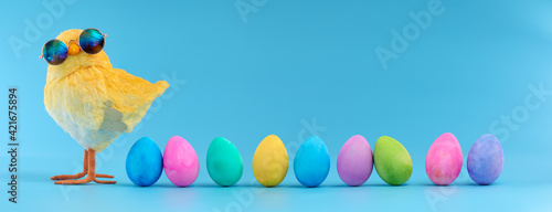 Easter decoration of a yellow chick wearing silly sunglasses with a row of colorful painted Easter eggs Fototapet