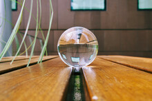 Close-up Of Crystal Ball On Bench Against Building