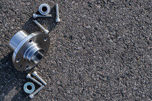Car Motor Parts. Auto Motor Mechanic Spare Or Automotive Piece On Dark Road Asphalt Background. Set Of New Metal Car Part. Black Bituminous Textured Waterproofing.