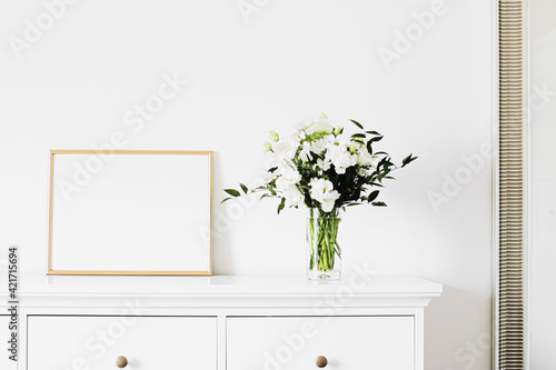 Obraz na plátně Golden horizontal frame and bouquet of fresh flowers on white furniture, luxury