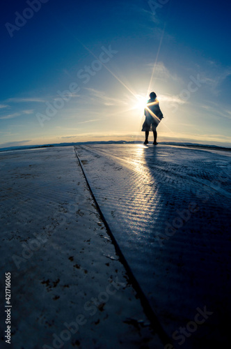 Photographie Silhouette Woman On A Rood Against Sky During Sunset