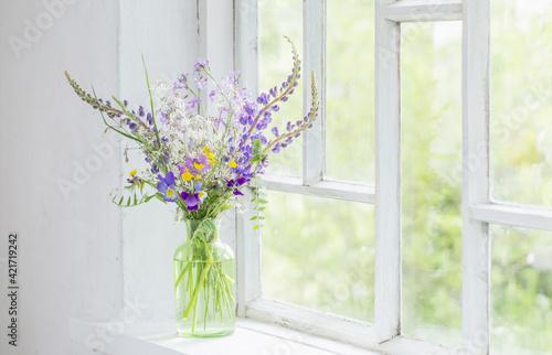 wild flowers in vase on white windowsill Fotobehang