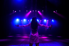 Unrecognizable Singer Standing On Stage At Microphone, Back View, Neon Lights