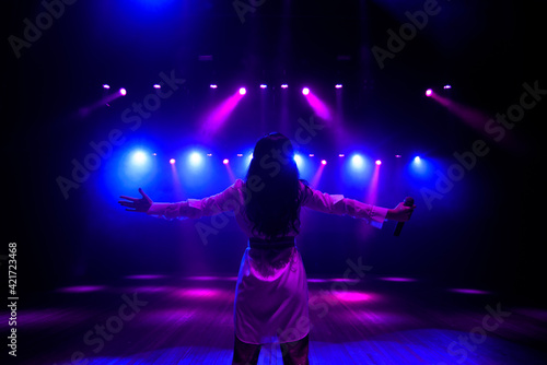 Fototapeta Unrecognizable singer standing on stage at microphone, back view, neon lights obraz