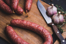Homemade Sausage On Cutting Board, Garlic Knife And Rosemary Branch, Top View