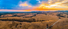 Rural Road Passing Through Agricultural Fields Towards Hills Silhouettes At Sunset - Aerial Panorama