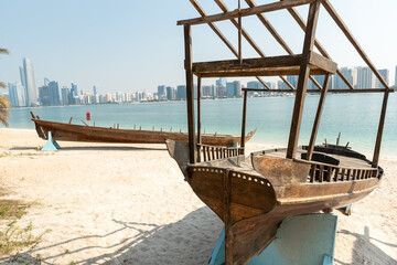Closeup of old wooden boats at the Heritage Village with Abu Dhabi skyline in the background