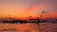 Silhouette Fishing Net In Sea Against Orange Sky
