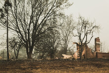 Some Portion Of A Building And Chimney Stack Remains After Wildfire Blows Through Town.