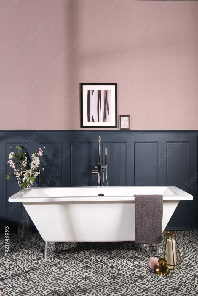 Fototapeta Bathtub in a bathroom with dark blue and pastel pink walls and patterned ceramic tile flooring