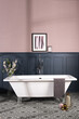 Bathtub in a bathroom with dark blue and pastel pink walls and patterned ceramic tile flooring