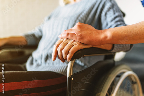 Fototapeta Cropped Hand Consoling Woman Sitting On Wheelchair obraz