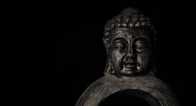Close-up Of A Meditating Buddha Statuette With Closed Eyes Isolated On Black Background