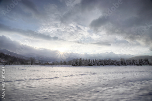 KARPACZ, POLAND - JANUARY 07, 2021: Beautiful winter landscape from the vicinity of Karpacz during the beginning of the sunset. View towards Sniezka and Mala Kopa. Giant Mountains, Poland, Europe.