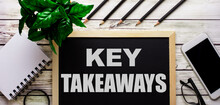 KEY TAKEAWAYS Is Written In White On A Black Board Next To A Phone, Notepad, Glasses, Pencils And A Green Plant.