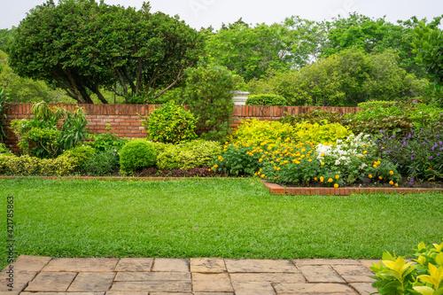 Backyard English cottage garden on brown pavement and green lawn Fotobehang