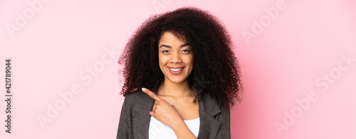 Young african american woman over isolated background pointing to the side to present a product