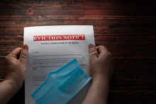 A Woman Holds An Eviction Notice For Non-payment. Financial And Housing Problems During The Lockdown. Free Space For Text. Partial Blur.