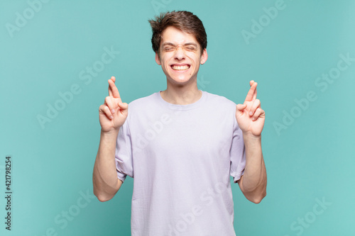 young boy smiling and anxiously crossing both fingers, feeling worried and wishi Wallpaper Mural