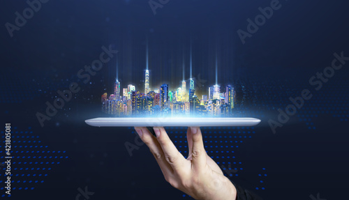 Futuristic city on digital tablet technology concept of businessman hand holding tablet, smart city internet of things abstract art blue background of internet network connection communication concept