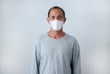 Asian Senior Man Standing Wearing Face Mask In Casual T-shirt Against On Grey Background