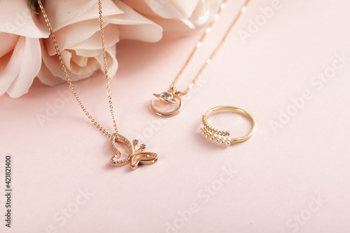 Fotografia High angle shot of a beautiful ring and necklaces on a pink surface