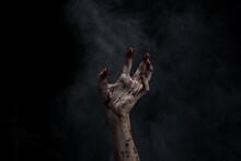 Bloody And Dirty Zombie Hand Rising Up From The Soil.  Hand Rising Out Of A Graveyard. Black Background And Smoke.