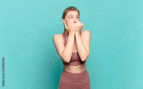 Photo young blond woman looking worried, anxious, stressed and afraid, biting fingernails and looking to lateral copy space