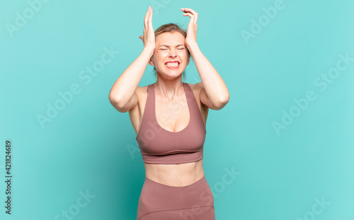 Fototapeta young blond woman feeling stressed and anxious, depressed and frustrated with a headache, raising both hands to head. sport concept obraz