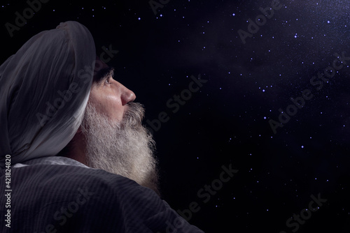 Foto A senior man in a turban is associated with a Muslim standing in dark smoky background light ray from above