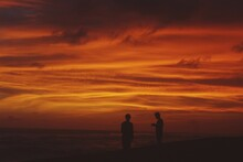 Silhouette People Standing On Land Against Orange Sky