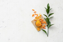 Turmeric Pills And Bowl With Powder On Light Background