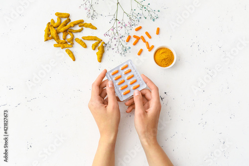 Valokuvatapetti Female hands and blister pack with turmeric pills on light background