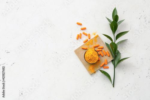Fototapeta Turmeric pills and bowl with powder on light background obraz na płótnie