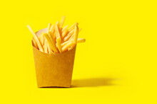 Paper Box With Tasty French Fries On Color Background