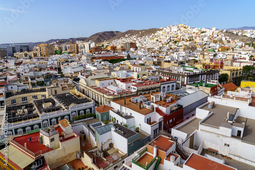 Aerial view of the city of Las Palmas, small white and brightly colored houses by the sea with blue sky and sunny day. Gran Canaria.
