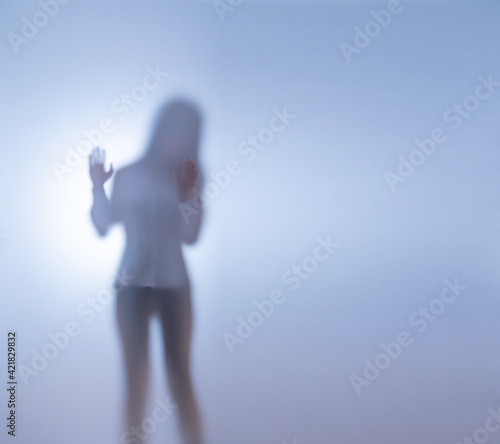 Fotografie, Obraz A young woman stands behind frosted glass