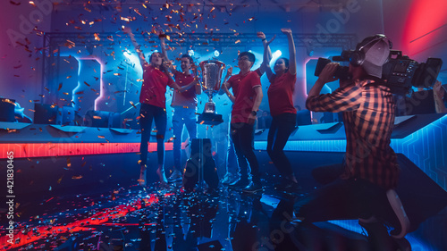 Fotografie, Obraz Diverse Esport Team Winner of the Video Games Tournament Celebrates Victory Cheering and Holding Trophy in Big Championship Arena