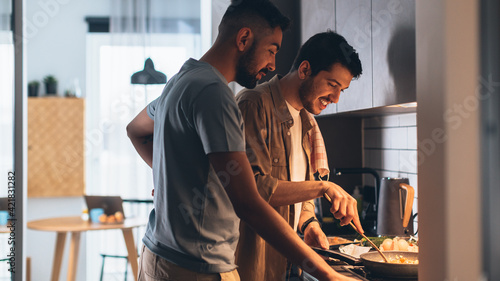 Fototapeta Happy Gay Couple Cooking Together in the Kitchen. Two Boyfriends in Love Spending Time Together. Boys Preparing Delicious Meal, Talk, Laugh and Have Fun. Authentically Tender Young Family Moment obraz