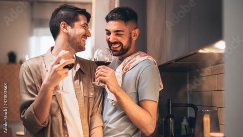 Fotografia Happy Gay Couple in Love Drink Wine, Chat, Prepare Delicious Dinner Meal