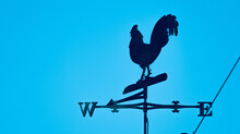 Rooster Weather Vane On The Roof Against A Blue Sky