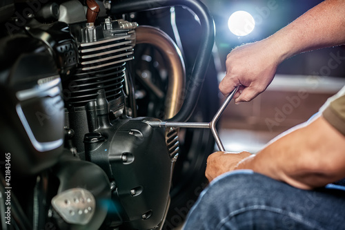 mechanic repairing motorcycle using wrench or socket on the engine of motorcycle , maintenance,repair motorcycle concept in garage