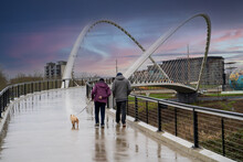 A Man And Woman Walking With Dog Across The Peter Courtney Minto Island Pedestrian Bridge In Salem, Oregon