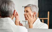 Close Up Of Mature Woman Applying Cream With Hand In Front Of A Mirror