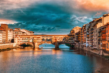 Bridge Over River By Buildings Against Sky In Florence