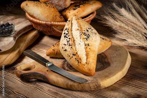 Fototapeta Fresh bread rolls on a rustic wooden table. obraz