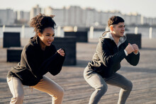Healthy Lifestyle. Stretching Exercises On The Embankment In The City Center. A Couple In Love Shows A Workout. Cardio Training Sports Young People. Comfortable Sportswear.